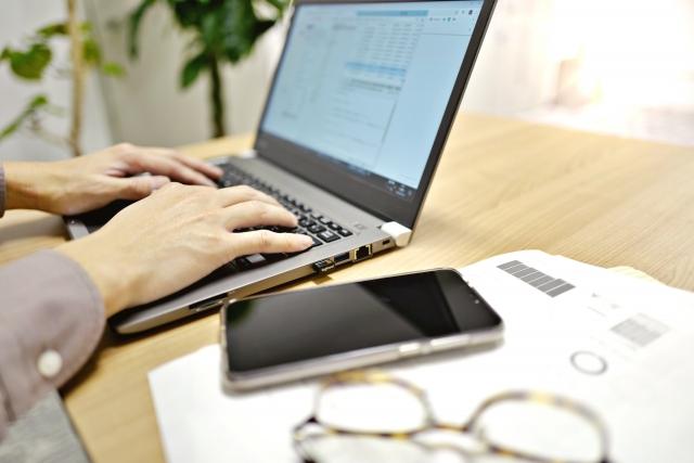 テレワークイメージ。リビングのテーブルでPパソコンをいじっている人。
